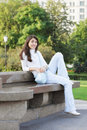 Young woman in a park looking sideway sitting on the bench Stock Photos
