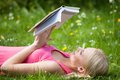 Young woman in park reading book happy beautiful lying on grass Royalty Free Stock Image