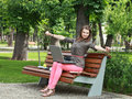 Young woman in a park sitting on bench with laptop during short break of her work Royalty Free Stock Photo