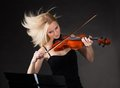 Young woman passionately playing violin over black background Royalty Free Stock Photo