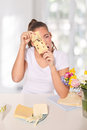 Young woman peeping through a cheese with holes Royalty Free Stock Photo