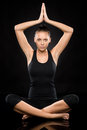 Young woman performing yoga with raised hands Royalty Free Stock Image