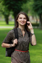 Young woman on the phone in a park with backpack using mobile Royalty Free Stock Photography
