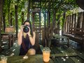 Young woman photographer taking picture in the cafe Royalty Free Stock Photo
