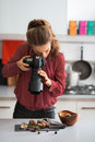 Young woman photographing food in kitchen Stock Photography