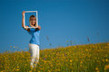 Young woman with picture frame in the countryside in spring Stock Images