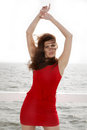 Young woman on the pier wind in hair red dress morning summer holiday Stock Photo