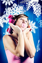 Young woman in pink curlers and pink dress is blowing a bubble from pink bubble gum bizarre looking at fake christmas paper Royalty Free Stock Photography