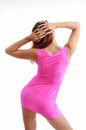 Young woman in the pink dress is posing rosy sheath short her body is bent her arms is raised behind head Royalty Free Stock Photos