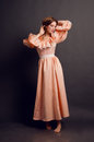 Young woman in a pink retro dress studio full length portrait of pretty Royalty Free Stock Image