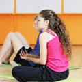 Young woman in pink shirt in a gym women sitting on mat looking sideways while gripping her wrist Stock Photo