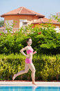 Young woman in pink sportswear runs along poolside smling Royalty Free Stock Image