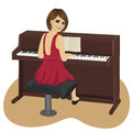 Young woman playing brown upright piano looking over shoulder Royalty Free Stock Photo