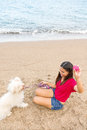 Young woman playing with dog beautiful asian on beach near sea Stock Photography