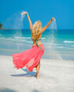 A young woman playing with sand as she dances along the beach Stock Image