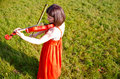 A young woman playing a violin in nature surrounded by on sunny day Royalty Free Stock Image