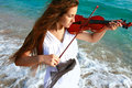 Young woman playing violin on sea background Royalty Free Stock Photo