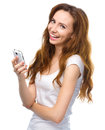 Young woman is pleased by incoming message cheerful on her phone isolated over white Royalty Free Stock Images
