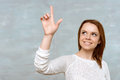 Young woman pointing upwards with her index finger Royalty Free Stock Photo