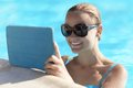 Young woman in a pool using tablet computer swimming as she stands at the edge her sunglasses smiling as she reads the screen Stock Image