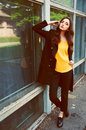Young woman portrait in black trenchcoat and yellow blouse with long brown hair dressed Stock Photo