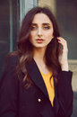 Young woman portrait in black trenchcoat and yellow blouse with long brown hair dressed Stock Images
