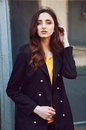 Young woman portrait in black trenchcoat and yellow blouse with long brown hair dressed Royalty Free Stock Photo