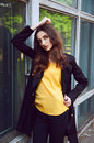 Young woman portrait in black trenchcoat and yellow blouse with long brown hair dressed Royalty Free Stock Photography