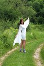 Young woman portrait happy caucasian brunette in white dress walking on green rural road Stock Photos
