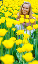 Young woman portrait in the park of with yellow tulips Stock Images