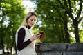 Young woman portrait in summer. Blonde girl is reading message on cell phone outside in city nature. Female with telephone. Royalty Free Stock Photo