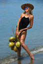 Young woman posing at the tropical beach with coconuts smiling location wearing black swimsuit sunglasses and hat and holding Stock Images