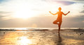 Young woman practicing yoga on the beach at sunset meditation Royalty Free Stock Photos