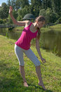 The young woman practicing yoga by the lake is engaged in eastern culture Stock Photos