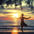 Young woman practicing yoga in the rays of the surrealist sunset at seaside silhouette a Stock Images