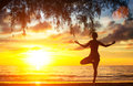 Young woman practicing yoga by the sea beach at sunset nature Stock Photo