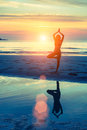 Young woman practicing yoga on sea beach at surrealistic sunset silhouette Stock Photos