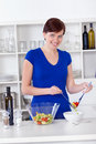 Young woman preparing healthy salad in her kitchen Royalty Free Stock Images
