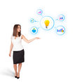 Young woman presenting light bulb with colorful graphs and diagr diagrams isolated on white Royalty Free Stock Photography