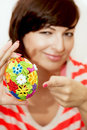 Young woman presents colorful easter egg smiling Royalty Free Stock Photos