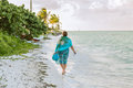 Young woman walking on the beach along the ocean Royalty Free Stock Photo