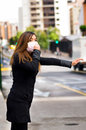 Young woman with protective mask on the street in the city with air pollution, asking for a taxi, city background