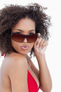 Young woman puckering her lips while holding her sunglasses Royalty Free Stock Image