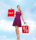 Young woman in purple dress and high heels beauty fashion shopping happy people concept with sale discount shopping bags Stock Image
