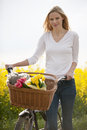 A young woman pushing a bicycle next to a seed field in flower Royalty Free Stock Photo
