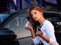 Young woman puts lipstick is reflected in the car door