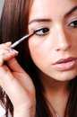 Young woman putting makeup. Royalty Free Stock Photos