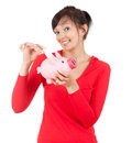 Young woman putting money into pink piggy bank Stock Photos