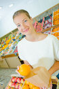 Young woman putting orange in paper bag Royalty Free Stock Photo