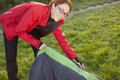 Young woman putting out sleeping bag from cover Fotos de archivo libres de regalías